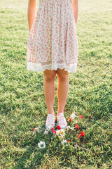 Young woman on green grass with flowers