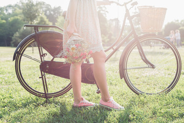 Woman with old fashioned bicycle and flowers