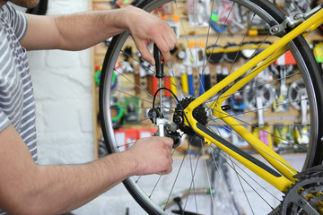 Young man working in bicycle repair shop, closeup