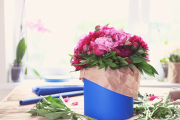 Gift carton with peonies on table in flower shop