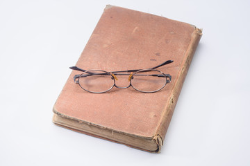 Old glasses on brown vintage book