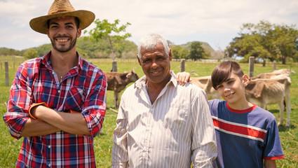Three Generations Family Portrait Of Farmers In Farm