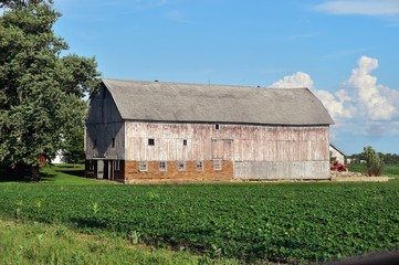 Veteran barn that has seen many seasons sits on a farm in Burlingtion, Illinois. The design on the large combination brick and wood structure is unusual for Illinois and the American Midwest.