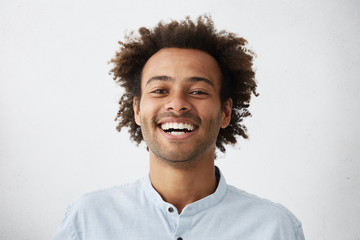 People, lifestyle, happiness and positive human expressions. Studio shot of attractive young dark-skinned student with Afro hairstyle laughing at good joke, looking at camera with carefree smile