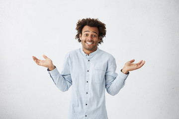 Portrait of uncertain careless young African-American employee wearing long shirt shrugging shoulders, feeling confused and doubtful about work, his expression saying I don't know, Who cares
