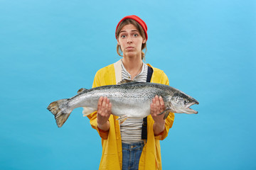 Studio portrait of beautiful female wearing red hat, yellow raincoat and jean overalls frowning her face while holding huge fish in hands. Successful angler with her catch. Hobby, recreation concept