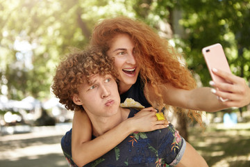 Outdoor portrait of curly male holding on back his girlfriend with freckled face and red hair looking at camera of cell phone, making selfie together. Positive redhead female and her boyfriend in park
