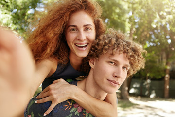 Love forever. Young redhead freckled female being on his boyfriend`s back and making selfie, embracing her lover smiling at camera. Curly young male is piggy backing his cute friend with freckles