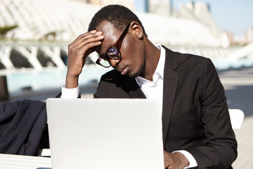 Tired black businessman in black suit and eyewear keeping hand on forehead while sitting at table outdoors working with laptop computer being busy with business report. Career and job concept