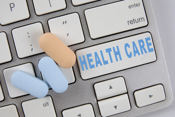 Medical pills on the keyboard with text HEALTH CARE. Medical Concept