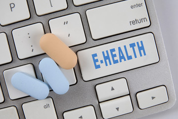 Medical pills on the keyboard with text E-HEALTH. Medical Concept