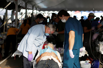 A dentist speaks with a man before extracting some of his teeth at the Remote Area Medical Clinic in Wise
