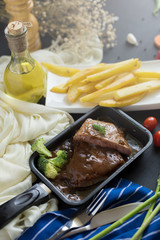 Fresh grilled meat. Grilled beef steak In the pan, French fries and Mashed potato with spoon, in serving bowl