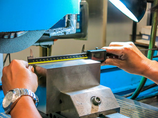 Technicians use digital counters to measure iron work from grinding. For precise quality control.
