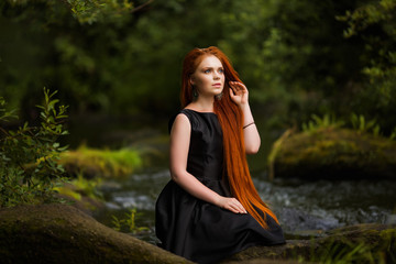 Young beautiful girl on the background of the extraordinary fantastic nature with long red hair