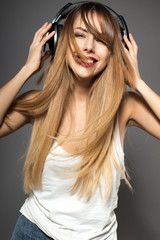 Awesome caucasian attractive sexy professional female model with long hair posing in studio wearing white shirt and wireless headphones, isolated on grey background