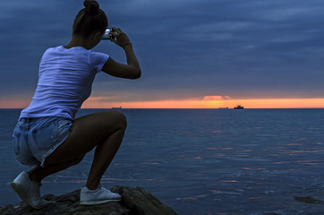 Silhouette of woman taking photo after sunset.