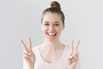 Indoor portrait of European girl isolated on gray background in casual clothes with optimistic smile, showing victory sign with both hands, looking friendly and willing to welcome and communicate.