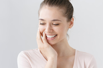 Indoor portrait of naturally beautiful young woman isolated on gray background with eyes looking down, being shy, touching cheek with hand in gesture of uncertainty and secrecy, looking feminine.