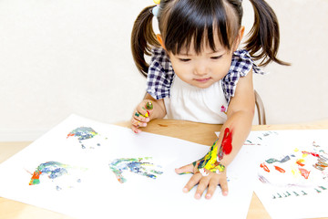 絵具で手形を付けて遊ぶ幼い女の子