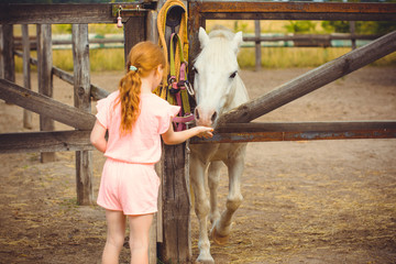 Little girl with red hair and pink costume with horses on a farm, pets animals in village in a rancho. Horses are human friends