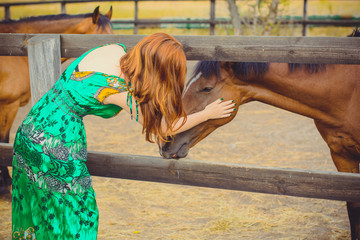 Woman with red hair and ornament green ethnic dress and with horses on a farm, pets animals in village in a rancho. Horses are human friends