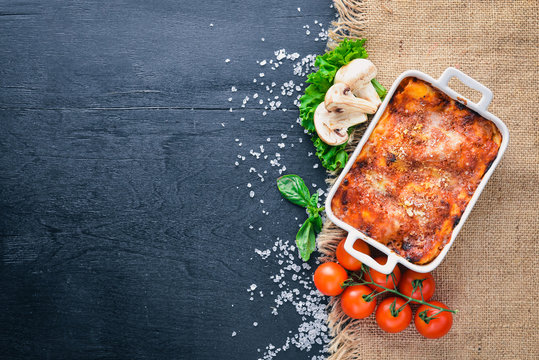 Lasagna with vegetables and cheese. On a wooden background. Top view. Free space for your text.