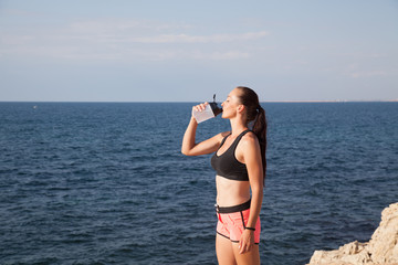 girl drinking water from a shaker after a workout on the beach