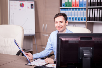 Smiling businessman in office looking at charts. Business and investment