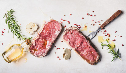 Aluminium Prints Meat Raw beef Striploin steaks with oil , spices and meat fork on white stone background, top view, flat lay, horizontal
