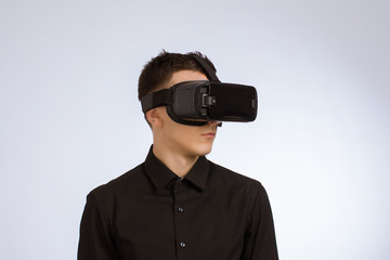 Young Handsome in Black Suit Wearing Virtual Reality Goggles. Iisolated on White Background