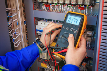 Electrical Engineer adjusts electrical equipment with a multimeter in his hand closeup.