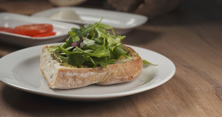 making italian sandwich with speck and mozzarella apply rocket salad