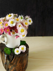 Bouquet of daisies in a white jug on a stump on a wooden background