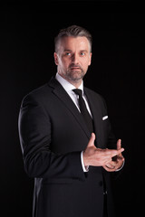 Portrait of adult confident businessman in studio photo on black background