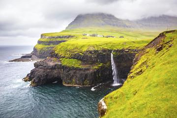Dramatic waterfall on Faroe Islands and the village Gasadalur