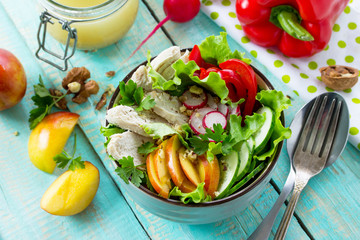 Summer lettuce with salad dressing vinaigrette. Salad with chicken, fresh vegetables, nectarine, walnuts and herbs on a kitchen wooden table.