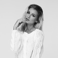 Beautiful pretty stylish blond woman with medium length straight hair posing in white pullover on white background. Bright fashion portrait