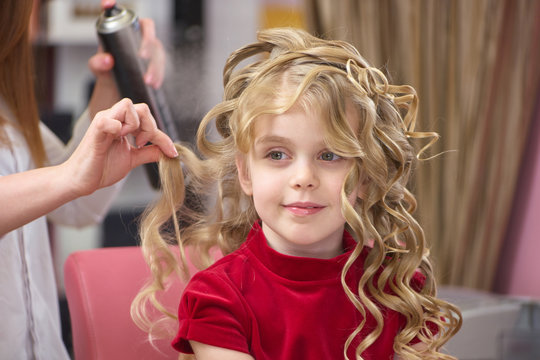 Little girl with curly hair. Kid at the hairdresser.