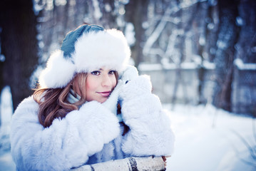 Beautiful girl in a winter snowy park