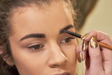 Hand using brow brush. Work of makeup artist.