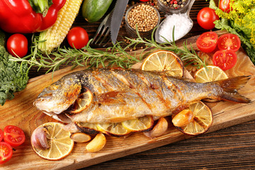 Roasted dorada fish with vegetables on wooden background