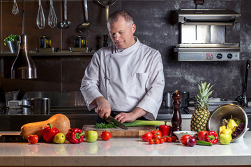 Chef cuts the vegetables into a meal. Preparing dishes. A man uses a knife and cooks.