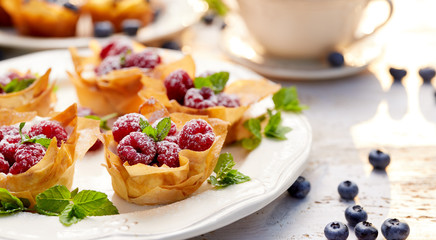 Photo sur Toile Dessert Phyllo cups with Mascarpone cheese filling topped with fresh Raspberries and mint on a white plate, delicious dessert
