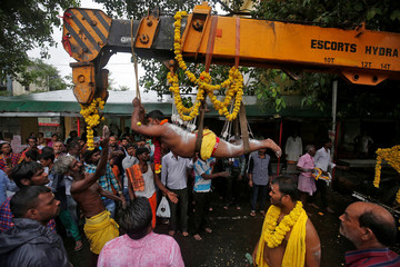 A Hindu devotee with his back and legs pierced with iron hooks suspends from a crane during an annual religious procession called Shitla Mata in Ahmedabad