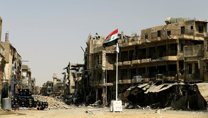 An Iraqi flag is seen amid destroyed buildings in the Old City of Mosul