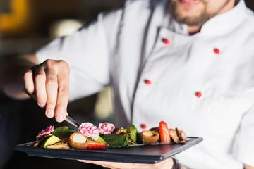 male cooks preparing meals in restaurant kitchen