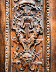 Old wooden gate engraved with demonic figures.