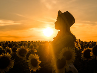 Silhouette of young beautiful blonde woman standing in sunflower field. Sunset background. Sexy sensual portrait of girl in straw hat and white summer dress.