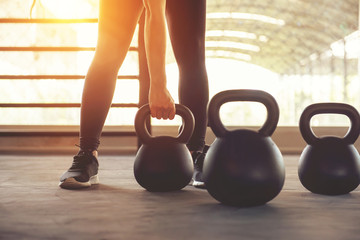 Papiers peints Fitness Fitness training with kettlebell in sport gym with sunlight effect.